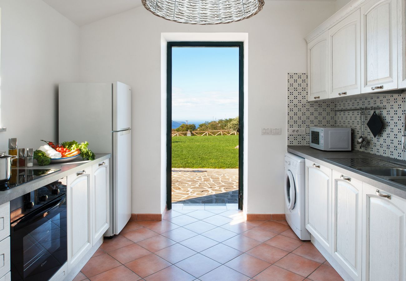 fully equipped kitchen and exit on the panoramic garden, casa del capitano, vacation villa massa lubrense, italy