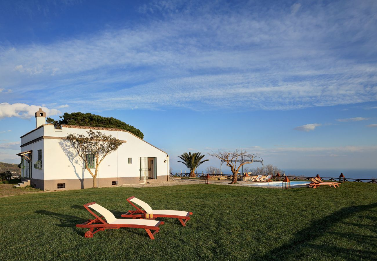 garden with two sunbeds and casa del capitano, holiday home massa lubrense, italy