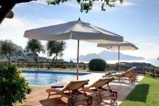 pool, sunbeds, sun umbrellas and capri island view, casale la torre, holiday apartments near sorrento, massa lubrense, italy
