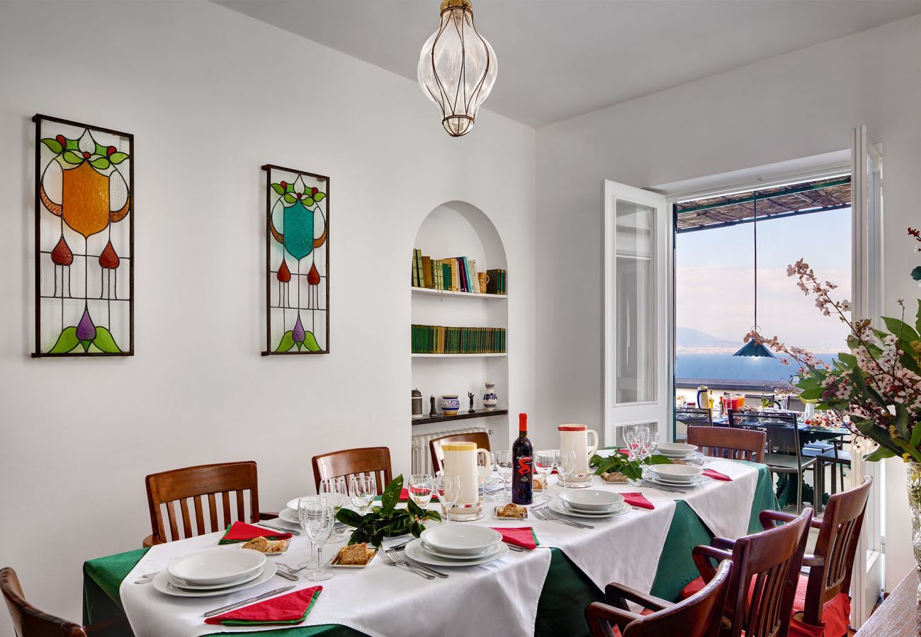 dining room with table and chairs, opened balcony, villa il gioiello, sorrento, italy