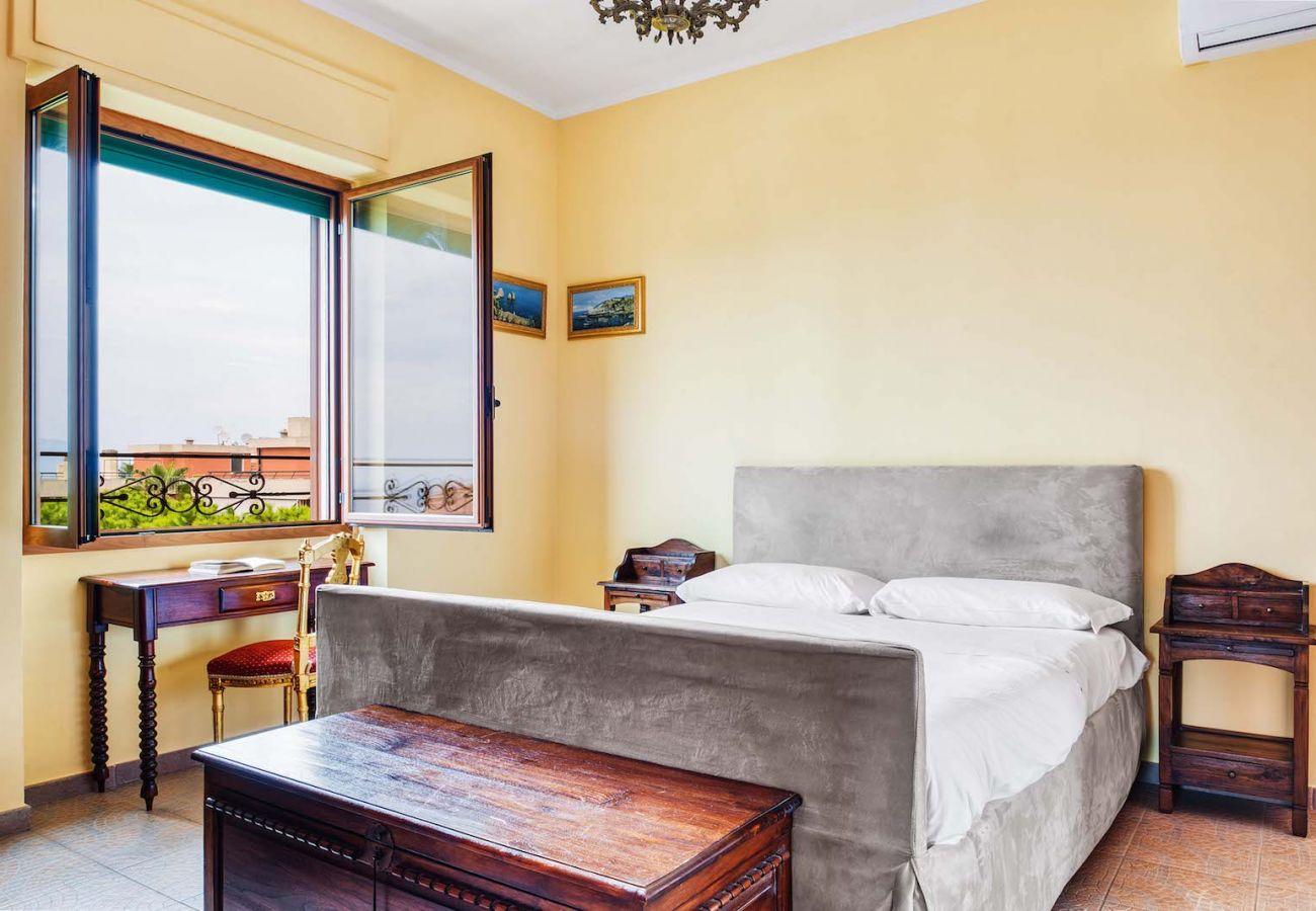 double bedroom, pastel yellow, opened window, la musica sorrento holiday apartment