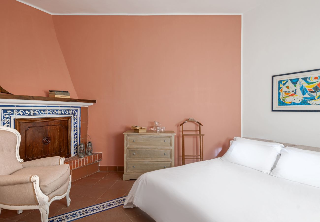 double bedroom with closed fireplace, villa alfonsina, massa lubrense, italy