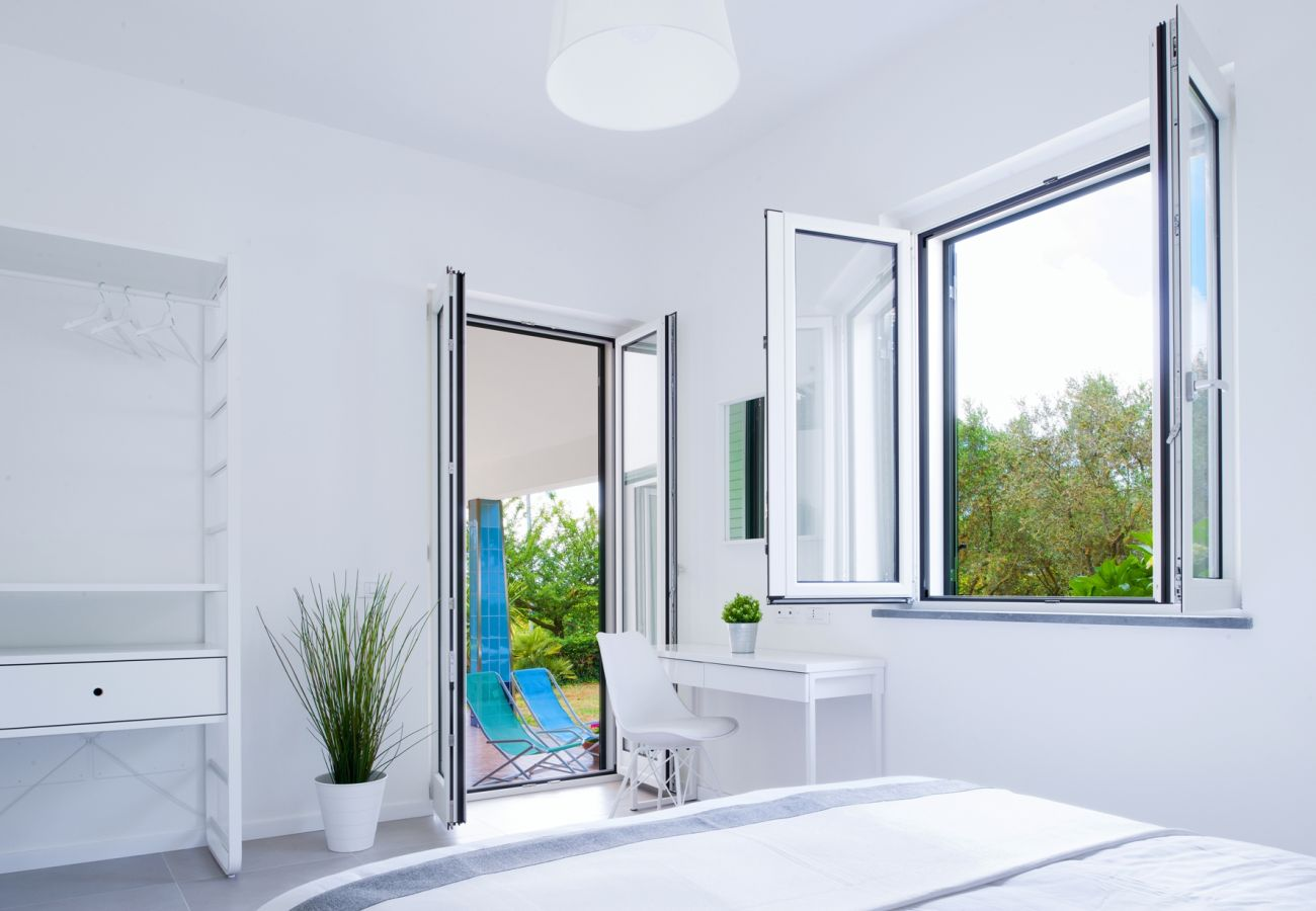 bright double bedroom at moring with opened window and door, vacation villa corinna, massa lubrense, italy