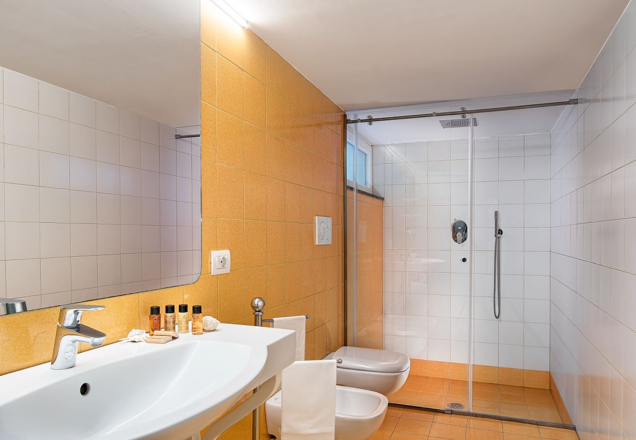 orange modern bathroom with shower cabin, vacation villa marinella, nerano, massa lubrense, italy