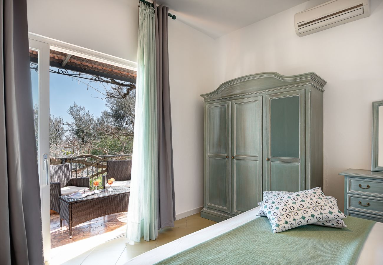 double bedroom with opened balcony and air-conditioner, vacation villa marinella, nerano, massa lubrense, italy