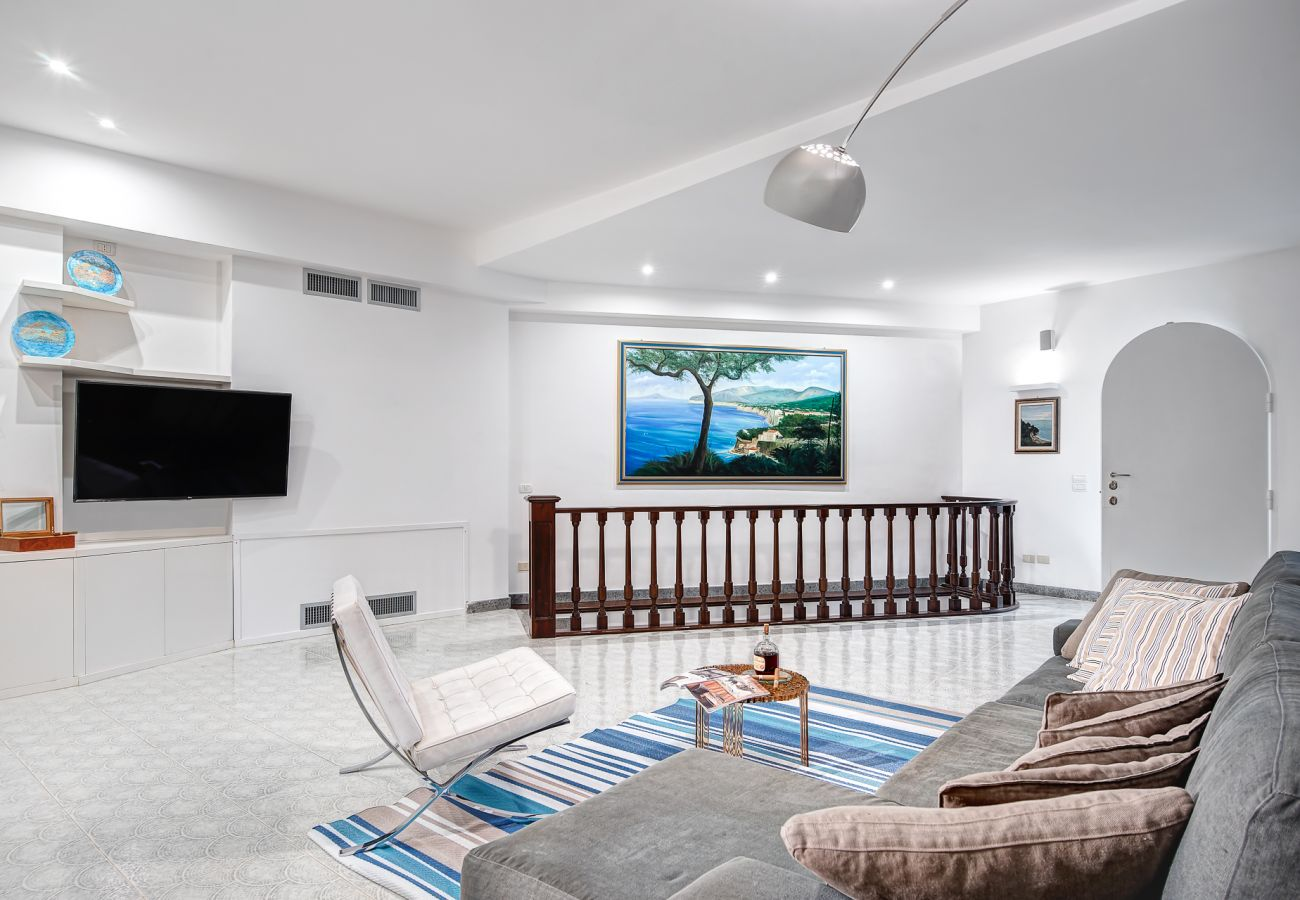 modern living room with wide TV and sofa, villa milena, sorrento, italy