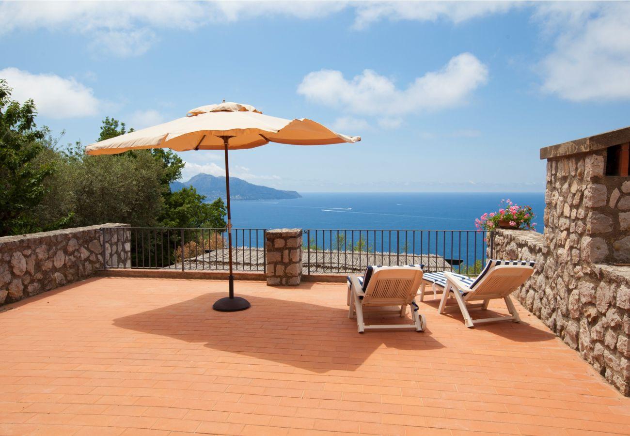 panoramic sea view terrace with sunumbrella and sun beds, holiday villa sterlizia, massa lubrense, italy