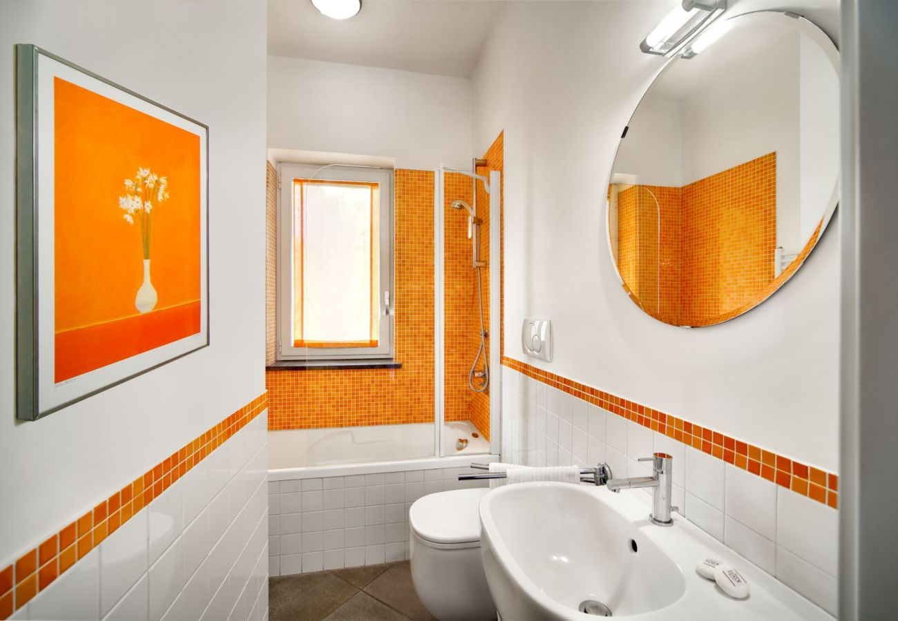 fully bathroom in orange, with tub and mirror, holiday apartment figaro, sant'agata sui due golfi, italy