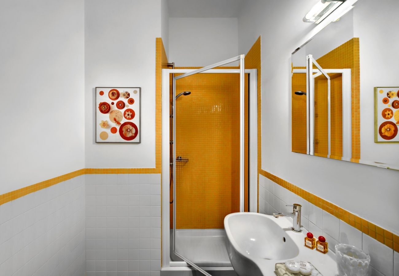 bathroom in oragne with shower cabin and mirror, holiday apartment figaro, sant'agata sui due golfi, italy