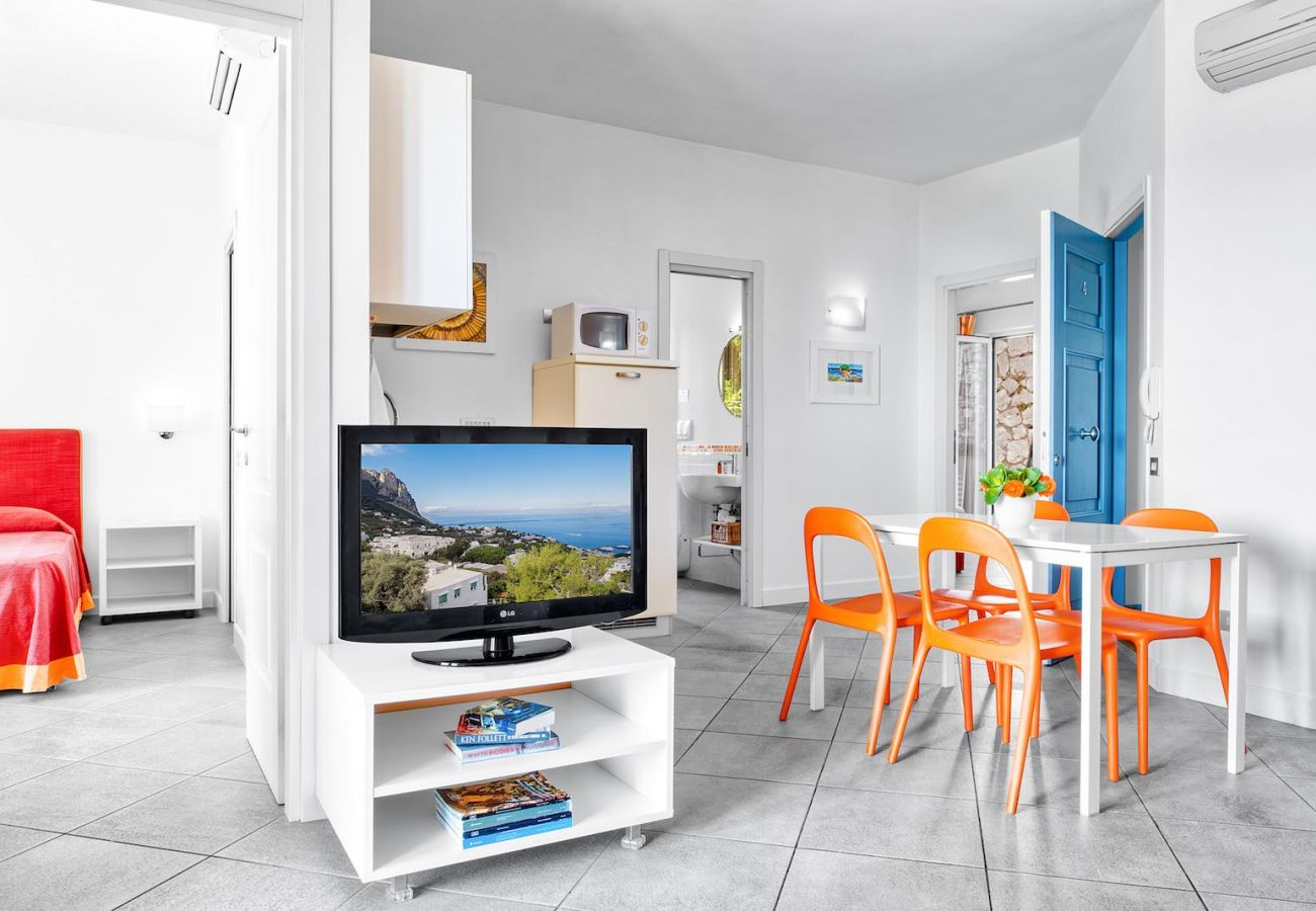 dining area with tv, orange chairs and table, figaro holiday apartment