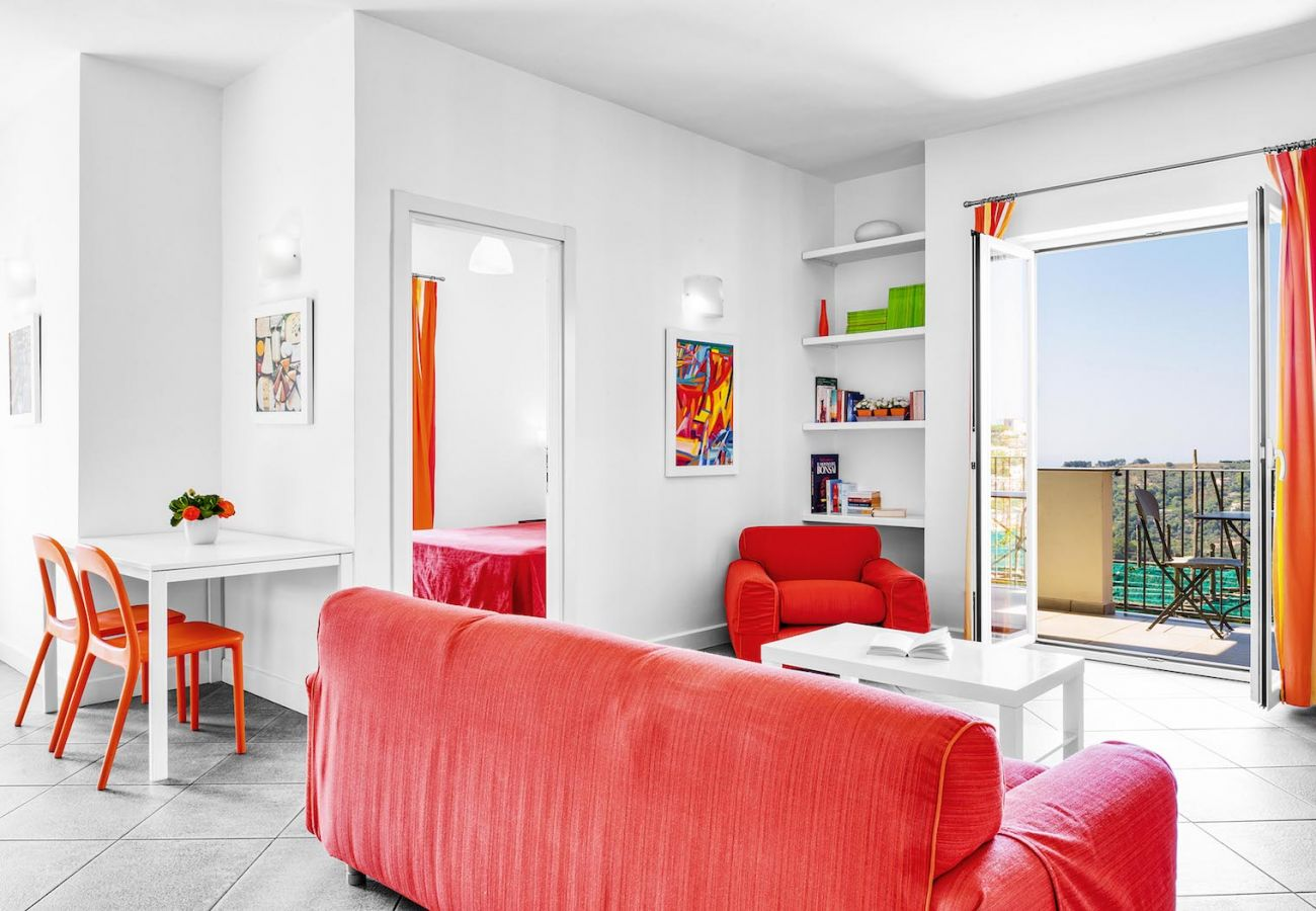 living area, in orange, with opened balcony, boheme holiday apartment