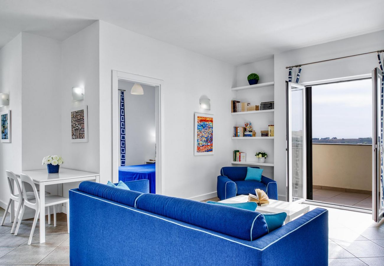 living area, in blu, with opened bright balcony, bedroom entrance, aida apt