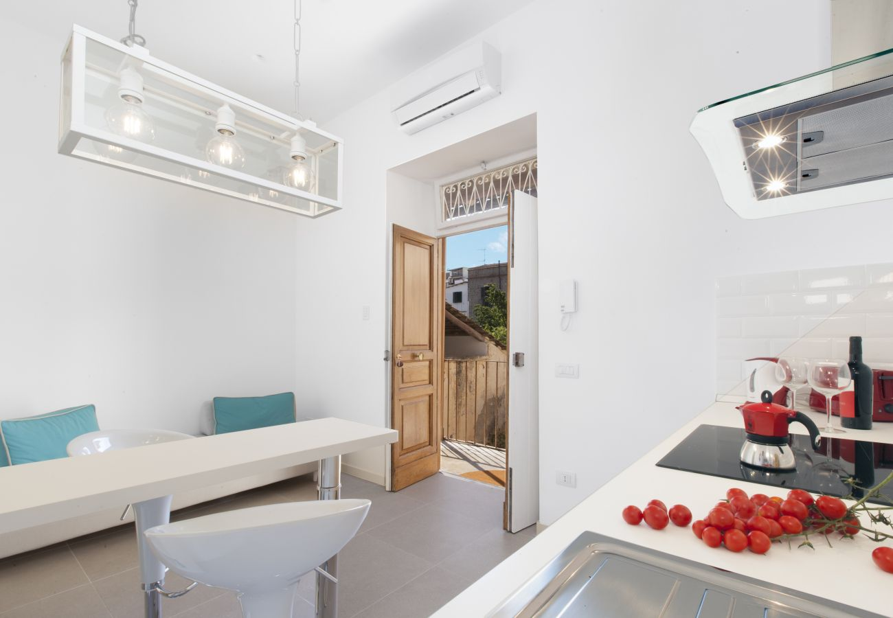 modern kitchen with modern sofa and opened door, holiday home blue suite, sorrento, italy
