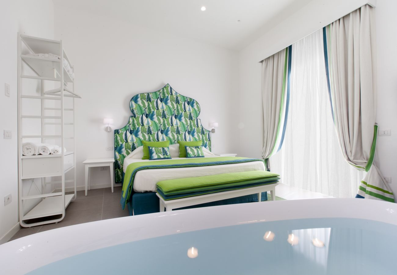 bright modern double bedroom with tub and balcony, holiday apartment green suite, sorrento, italy