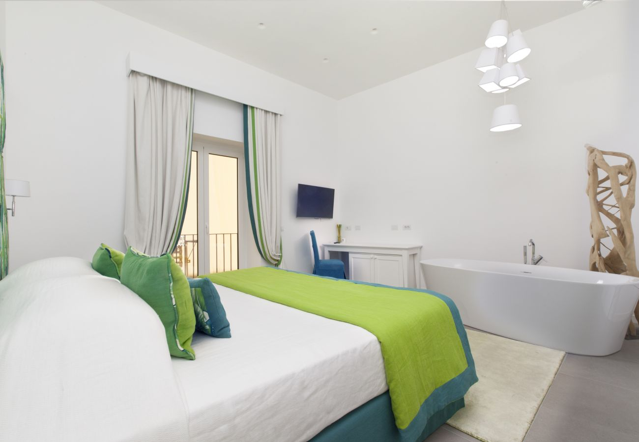 double bedroom with balcony, tv and tub, holiday apartment green suite, sorrento, italy