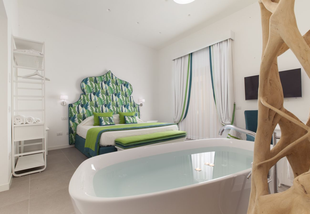 modern double bedroom in green, with tv and bath, holiday apartment green suite, sorrento, italy