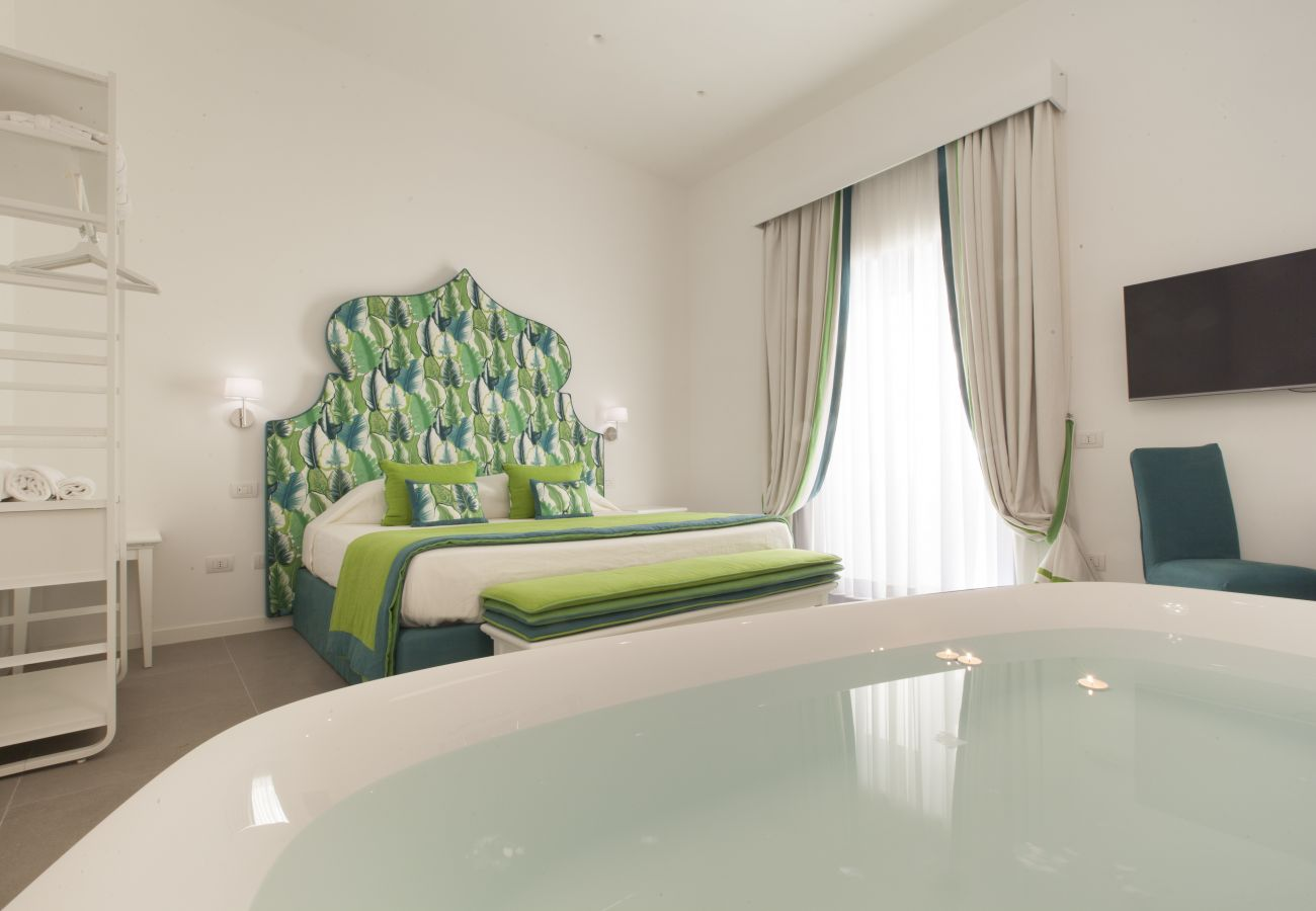 modern bright double bedroom in green with balcony and tv, holiday apartment green suite, sorrento, italy
