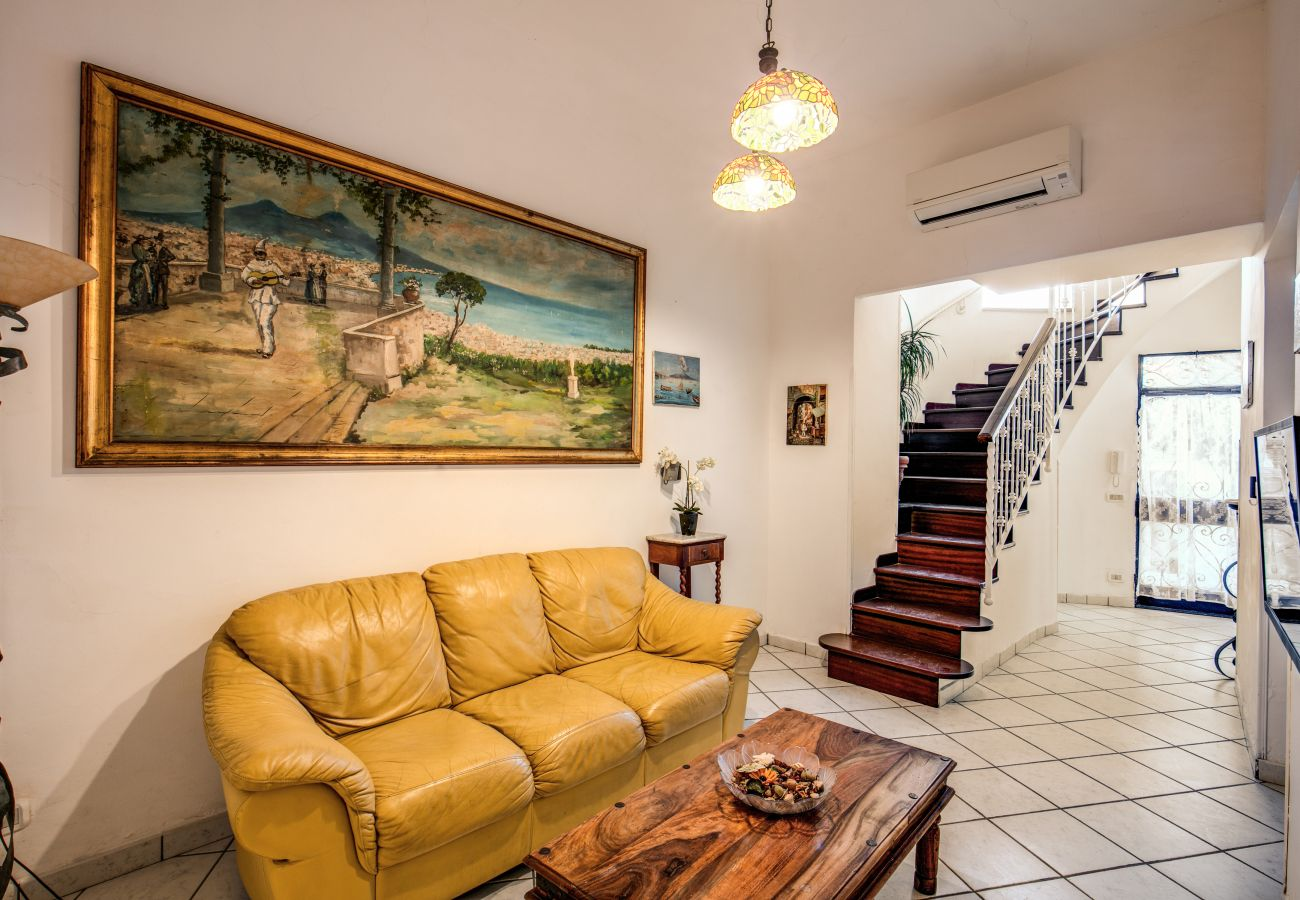living area with yellow sofa, air conditioner, tv and stairs