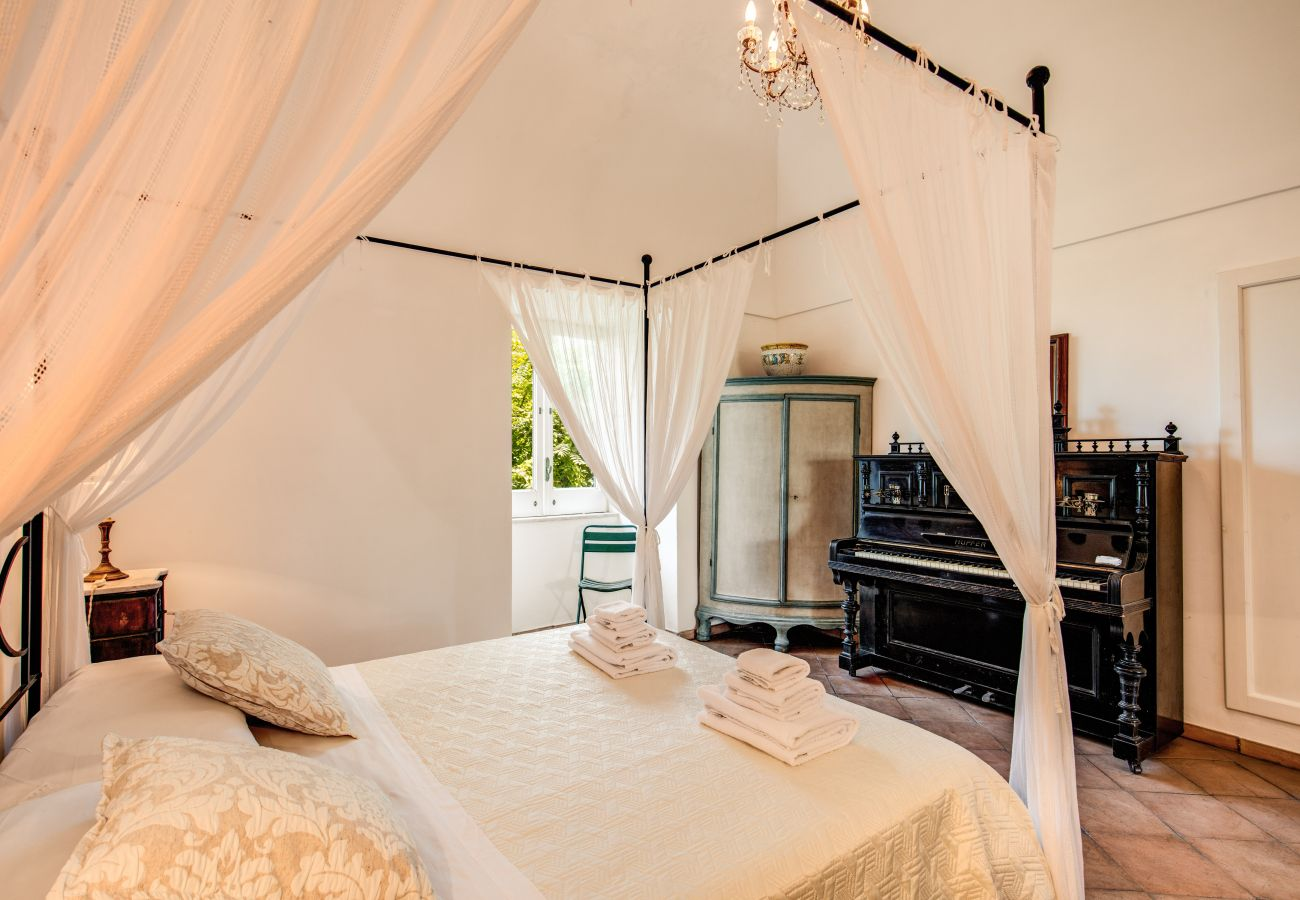 bright double bedroom with canopy bed and window