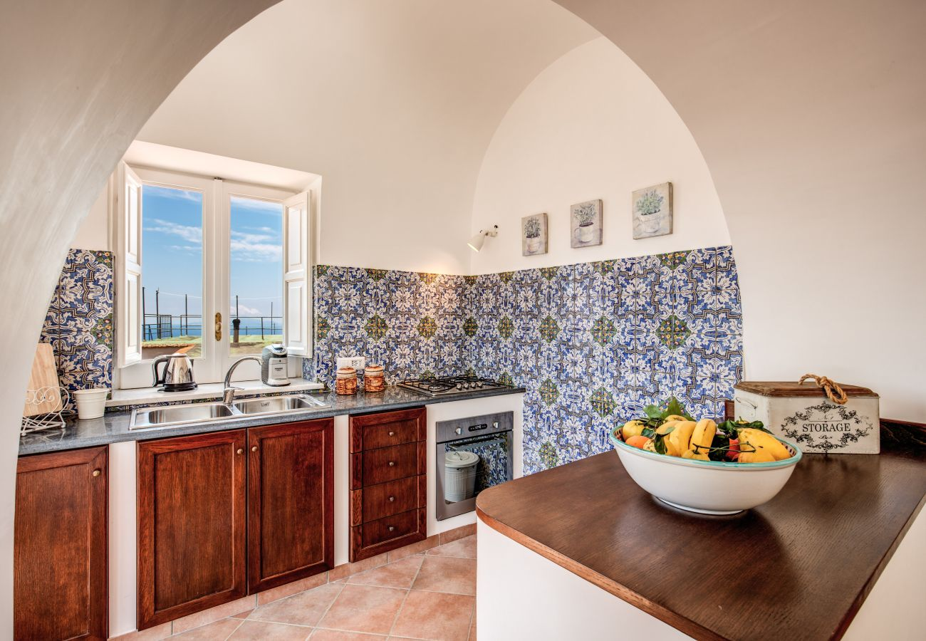 bright masonry kitchen, with oven and wooden furniture